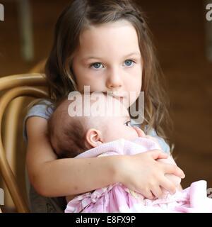 Girl (4-5 ans) de câlins petite sœur Banque D'Images