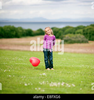 Girl (2-3) holding heart shaped balloon Banque D'Images