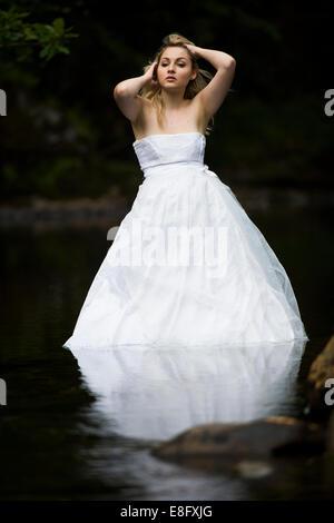 """La robe """"rebuts"""": une jeune femme blonde girl wearing white ball modèle mariée robe de mariage robe debout dans Banque D'Images"""