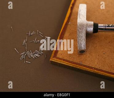 Close-up de punaises et d'un marteau à l'arrière de l'image encadrée récemment rénové Banque D'Images