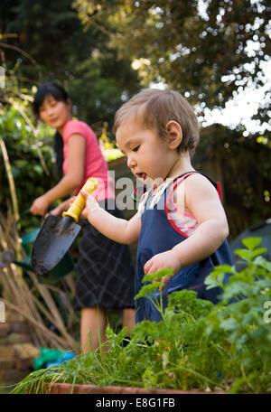 Une ethnicité mixte (East Asian / caucasian) female toddler dans le petit jardin urbain à la maison avec sa mère Banque D'Images