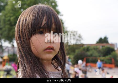 Portrait d'une jeune fille debout dans une aire de jeux Banque D'Images