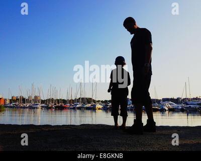 Stockholm, Suède, un garçon et son père de lancer des pierres dans l'eau et regarder les bateaux Banque D'Images