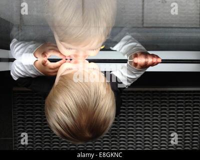 Stockholm, Suède, un petit garçon à la recherche à travers une fenêtre et voir son propre reflet Banque D'Images