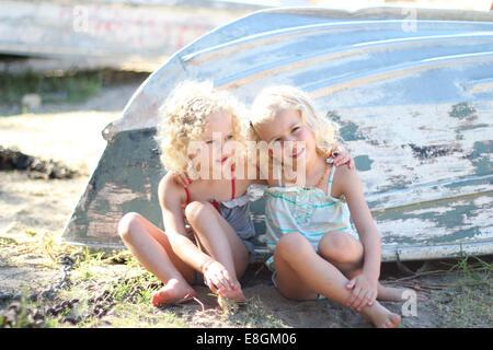 Portrait de deux jeunes filles assis par un bateau retourné Banque D'Images