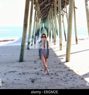 Femme debout sur la plage sous une jetée en bois, Carolina Beach, Caroline du Nord, États-Unis