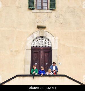 Père et trois enfants debout devant un bâtiment, Florence, Toscane, Italie