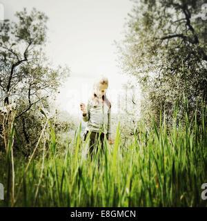 Fille debout dans un pré tenant une fleur sauvage