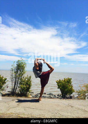 Girl doing yoga tirant bow permanent on beach Banque D'Images
