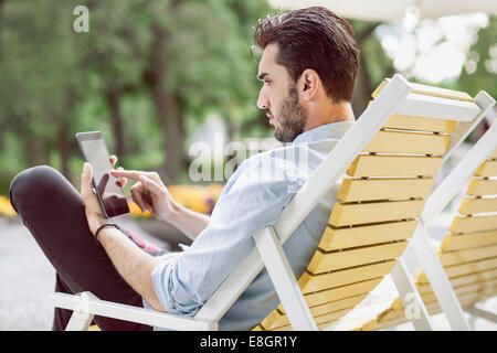 Young businessman using digital tablet on lounge chair at park Banque D'Images