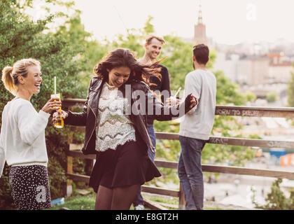 Amis de sexe féminin au cours de danse partie sur le roof garden Banque D'Images