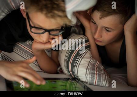 Deux garçons lying on bed using digital tablet Banque D'Images