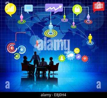 Groupe de gens d'affaires travaillant à l'Intérieur et des silhouettes d'un réseau mondial d'information à thème Banque D'Images