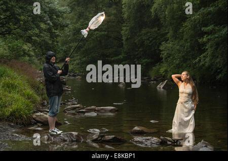Corbeille la robe photo shoot: un 'bride' de porter sa robe de mariage debout dans River - photographes sous la Banque D'Images