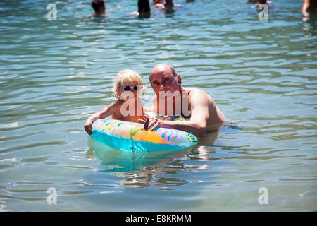 Une petite fille dans l'eau avec son père dans un petit bateau gonflable. Banque D'Images