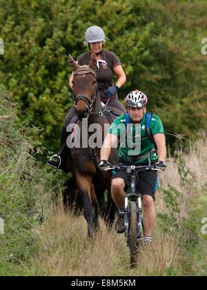 L'homme sur un vélo de montagne avec une femme sur un cheval le long d'un bridleway, Chettle, Dorset, UK Banque D'Images