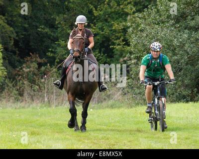 Femme sur l'équitation avec l'homme sur un vélo de montagne, Chettle, Dorset, UK Banque D'Images