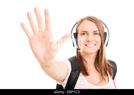 Belle jeune fille étudiante avec un casque tenant sa main vers le haut de faire un geste, cinq isolé sur fond blanc.