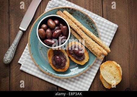 Du pain avec de la pate d'olive sur gros plan de la plaque. La cuisine grecque Banque D'Images