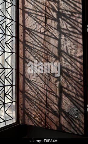 La lumière qui brillait à travers la fenêtre décorative sur l'obturateur en bois Banque D'Images