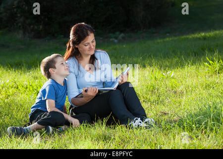 Jeune mère de lire une histoire à son fils assis sur une herbe verte dans le parc Banque D'Images