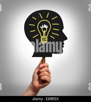 Concept de promotion de l'éducation et les droits des enfants à avoir accès à la formation et l'apprentissage scolaire abordable qu'une main tenant une pancarte en forme de signe comme une tête avec un dessin d'une ampoule comme une métaphore de la jeunesse social support.