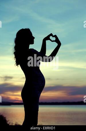 Mère enceinte rendant le cœur sign Banque D'Images
