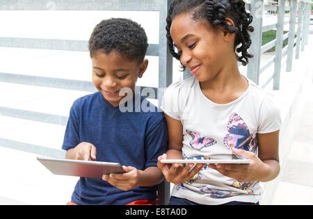 African American frère et sœur à l'aide de tablettes numériques Banque D'Images
