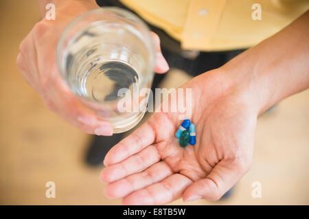 Close up of mixed race man holding medicine et verre de l'eau Banque D'Images