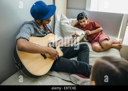 Mixed Race boy watching frère qui joue de la guitare dans la chambre Banque D'Images