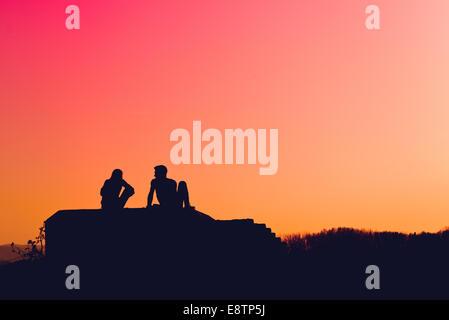 Silhouettes de young love couple sitting outdoors et parler à l'automne coucher du soleil Banque D'Images