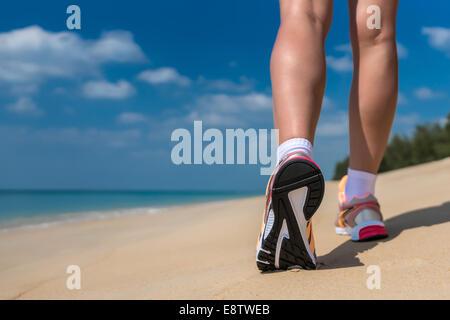 Close up de pieds d'un coureur s'exécutant dans la plage pour le marathon et la formation en santé bien-être remise Banque D'Images
