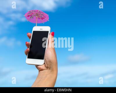 Main femme montrant téléphone mobile et cocktail parapluie sur le ciel en arrière-plan Banque D'Images
