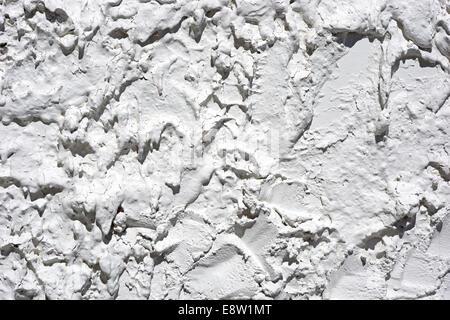 Un mur extérieur avec une épaisse couche de stuc peint en blanc avec des ombres. Banque D'Images
