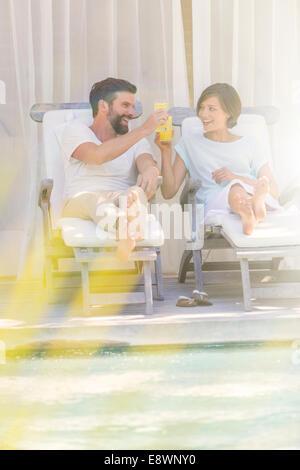 Couple toasting each other dans les chaises de parterre en piscine Banque D'Images