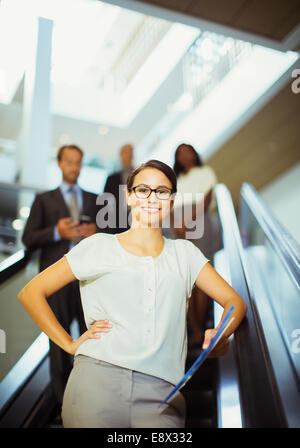 Businesswoman riding escalator in office building Banque D'Images