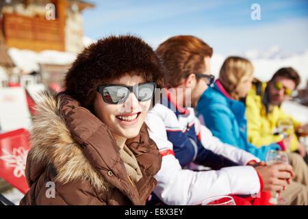 Femme assise avec ses amis dans la neige Banque D'Images