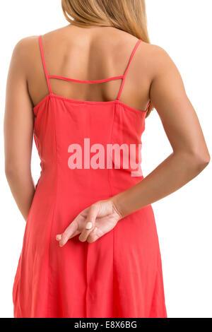 Close up de doigts croisés derrière le dos d'une femme Banque D'Images