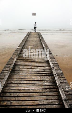 Teenage girl on old pier mer Banque D'Images