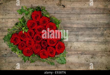 Bouquet de roses rouges en forme de coeur sur fond de bois rustique. Valentines Day concept. retro toned photo Banque D'Images