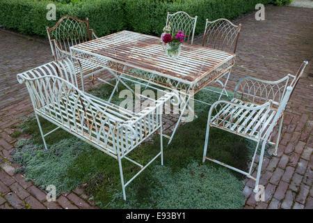 Table et chaises en métal élégant avec herb parquet sous à Jennifer Stratton's garden dans Codford, Wiltshire Banque D'Images