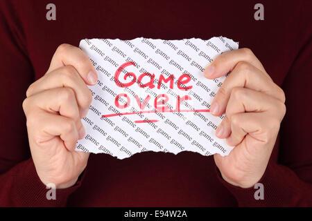 Morceau de papier rouge avec mot 'game over' sur l'arrière-plan avec les mots 'jeu' dans les mains de la femme. Banque D'Images
