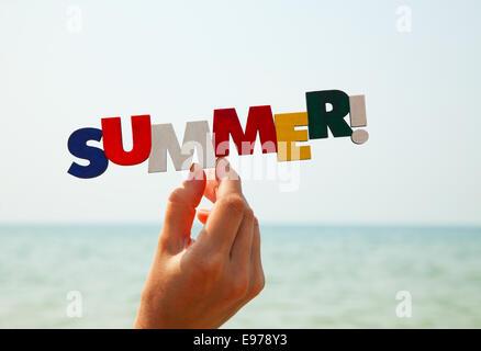 La main de femme tenant de l'été mot coloré Banque D'Images