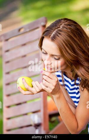 Femme avec les cheveux bruns smelling flower while holding an apple Banque D'Images