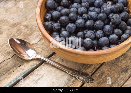 Dans l'argile fraîche prunellier bol avec silverspoon sur table en bois Banque D'Images