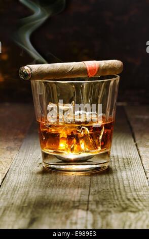 Cigare cubain brûlant posé sur un verre de brandy dans un bar, le luxe plaisirs d'un riche homme macho Banque D'Images