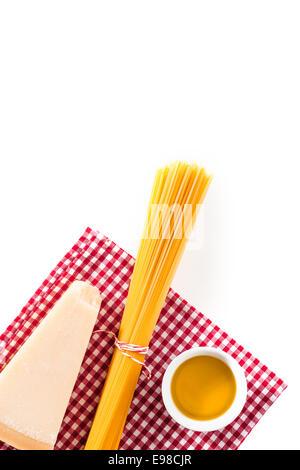 Coin de fromage italien avec un paquet de spaghettis non cuits et un petit bol d'huile d'olive sur un chiffon à Banque D'Images