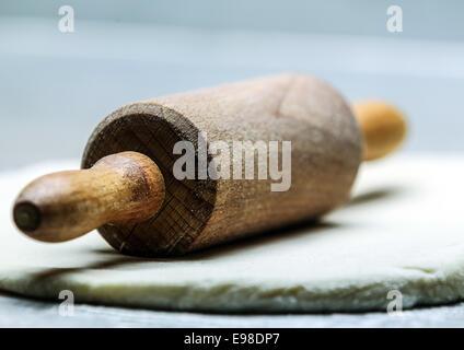 Close-up low angle view of an old-fashioned de rouleau à pâtisserie sur la pâte roulée ou pâtisserie reposant à un angle oblique avec la poignée vers l'appareil photo et peu profondes 6 Banque D'Images