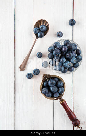 Vue de dessus de bleuets ou myrtilles dans une antique passoire du thé, bol en verre et cuillère sur une vieille table en bois blanc