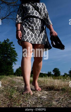 Les jeunes femmes marcher pieds nus dans un champ extérieur. Vigevano, Pavie. Italie Banque D'Images